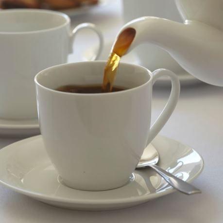 Ceai negru frunze in infuzie turnat din ceainic alb in ceasca de ceai din portelan