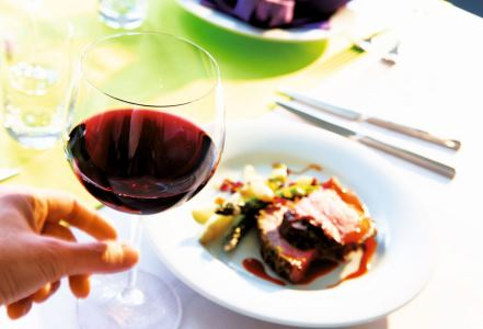 pahare de vin din cristal facute in moldova cu vin rosu langa farfurie cu mancare